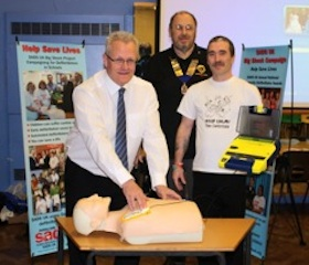 Robert Underwood of SADS UK, Bill Southworth of Redditch Lions present Tim Jones of Birchensale Middle School with the new life saving equipment