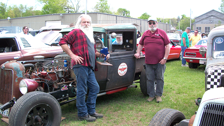"PHILLIPS AWARD — Charley Harley, left, of Guilford, Vt., stands next to his ""Rat Rod,"" a green hot rod pickup, which won the Dick Phillips Memorial Award at the recent car show at Silver Lake Park hosted by the North Quabbin Cruisers. Presenting the award was Dick Noel, right, vice president of the North Quabbin Cruisers. As is tradition, the trophy was hand made by Noel out of old used parts. This particular year the centerpiece was a gas nozzle."