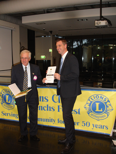 President Tony Philps (left) presents Warringah Mayor, Michael Reagan with a copy of the Club's 50th Anniversary History