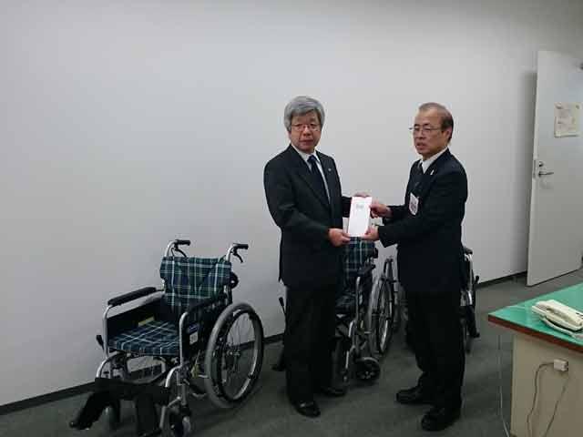 社会福祉協議会へ車椅子寄贈目録を差し出す