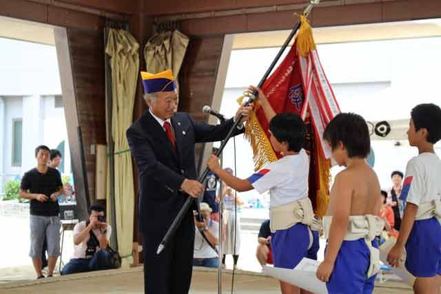 会長から優勝旗を受取る優勝者