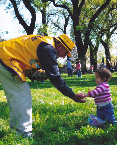 Lion Henk assisting a young participant at the Lions Easter Egg Hunt
