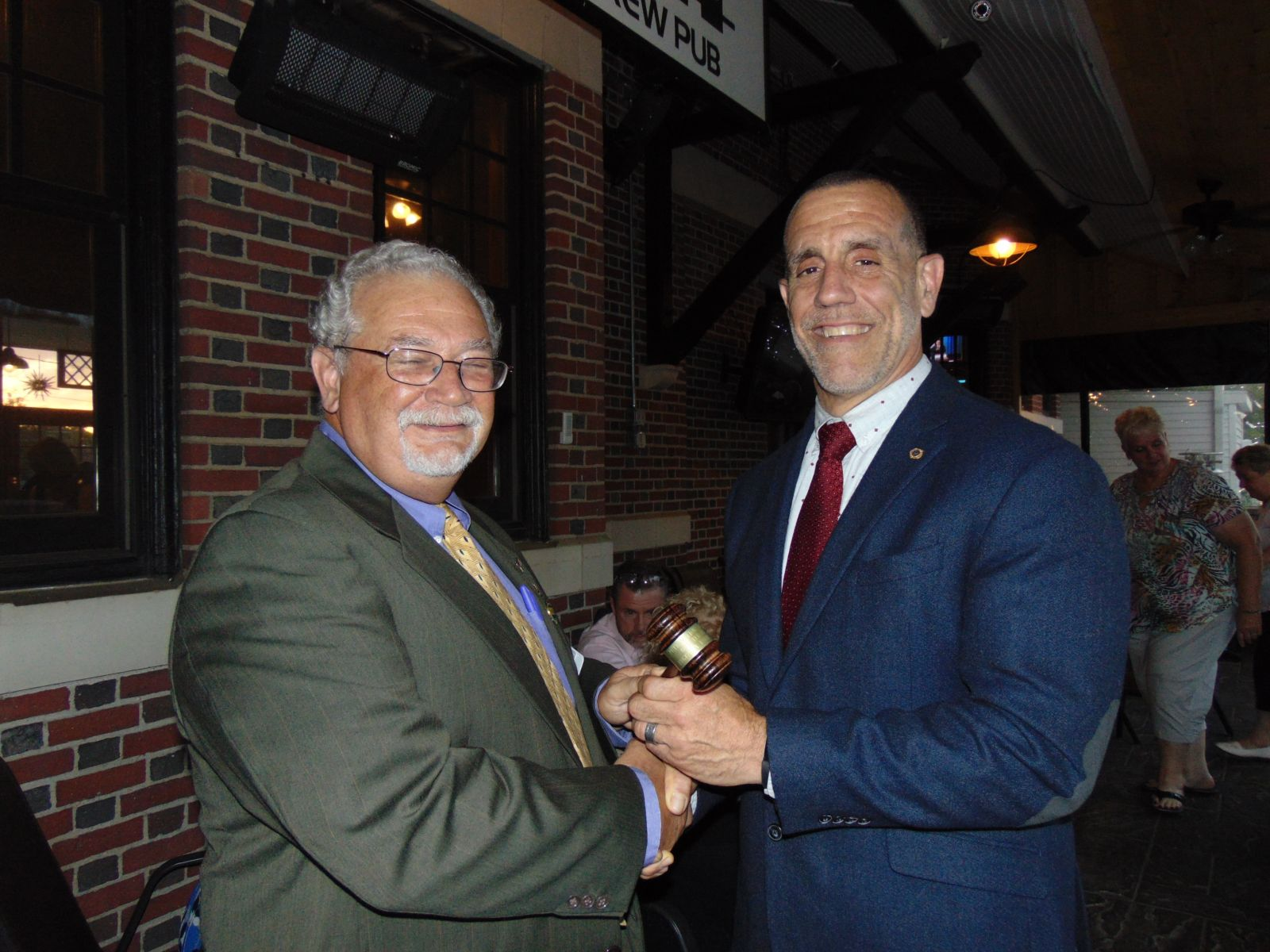 Past President Romeo Blackmar hands gavel to Incoming President Steve Faucher
