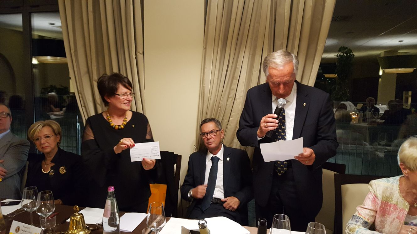 Il PDG Hermann dr. Gert consegna un assegno frutto del service del gemellaggio alla presidente Margherita Cecco durante la serata di apertura dell'anno 2017-2018.
