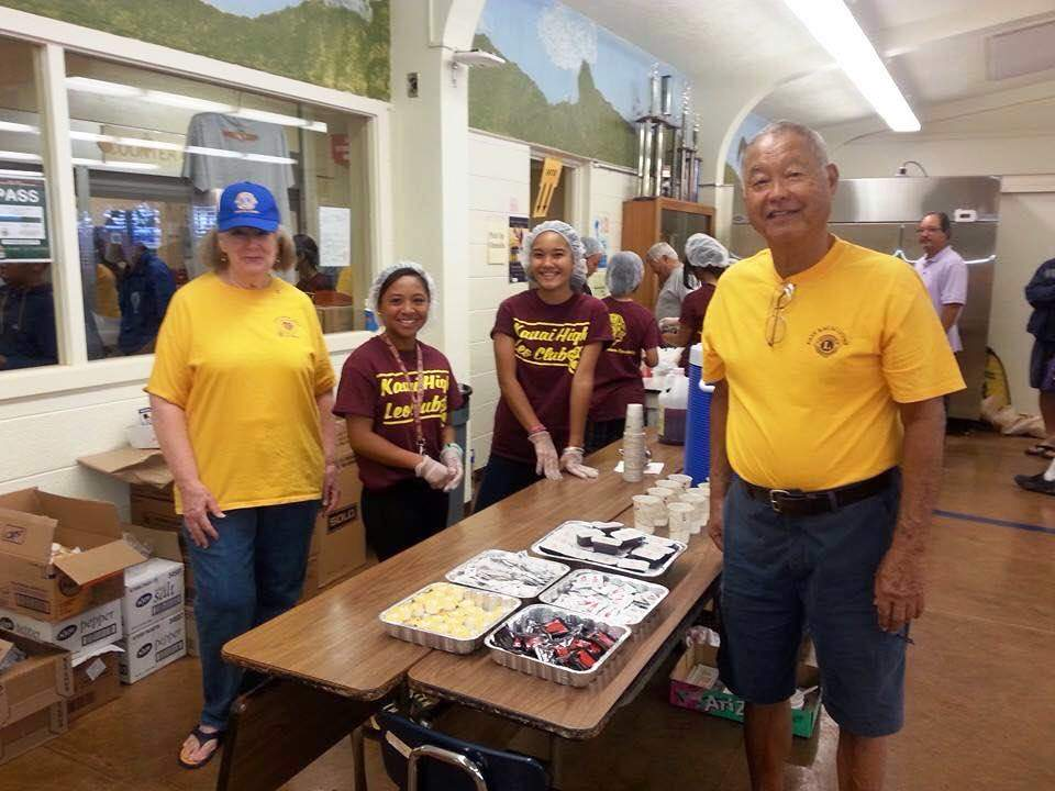 Lions Shirl Whitfield and Donald Nagamine pose with Kauai High Leos at the condiments station.