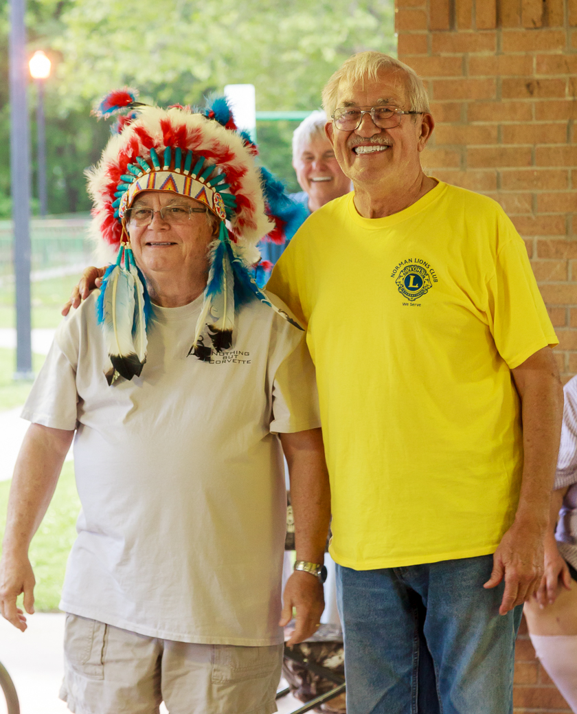 Outgoing President Duane Winegardner welcomes new President Alvin Cummings by passing on the ceremonial head-dress