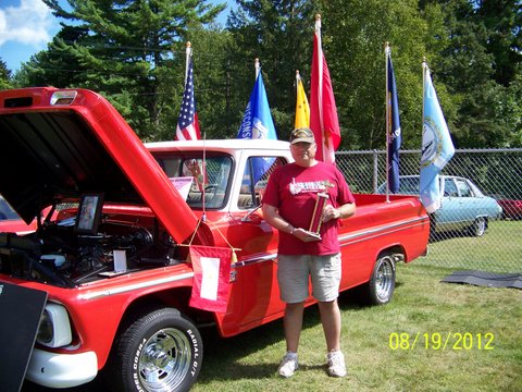 Brian Jopek standing with his trophy by his son's flag bedecked truck