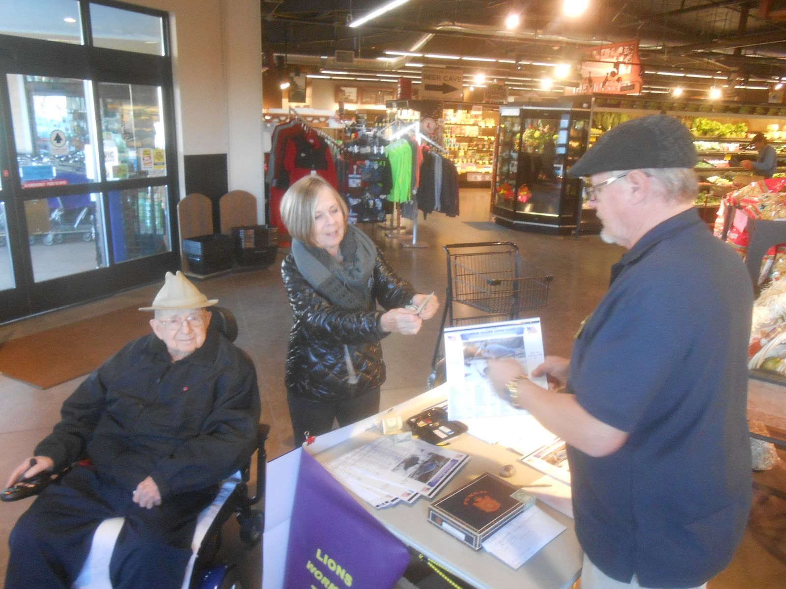 Lion Steve Westman sells a calendar to Connie Smith and her father Howard Harris.