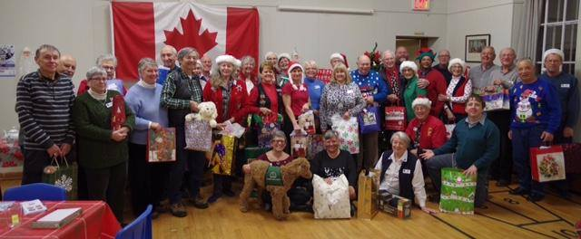 For the second year in a row, the Wellington District Lions Club has provided Christmas presants for seniors in long-term care who have no family and no gift to open on Christmas morning.  Pictured below are club members, friends and family and Guidedog Hudson.
