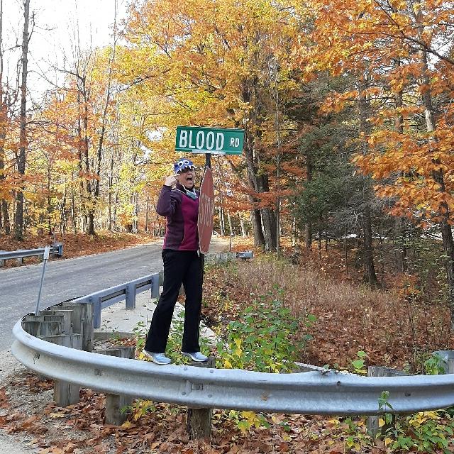 Participant finds Blood Road sign during Questival scavenger hunt.