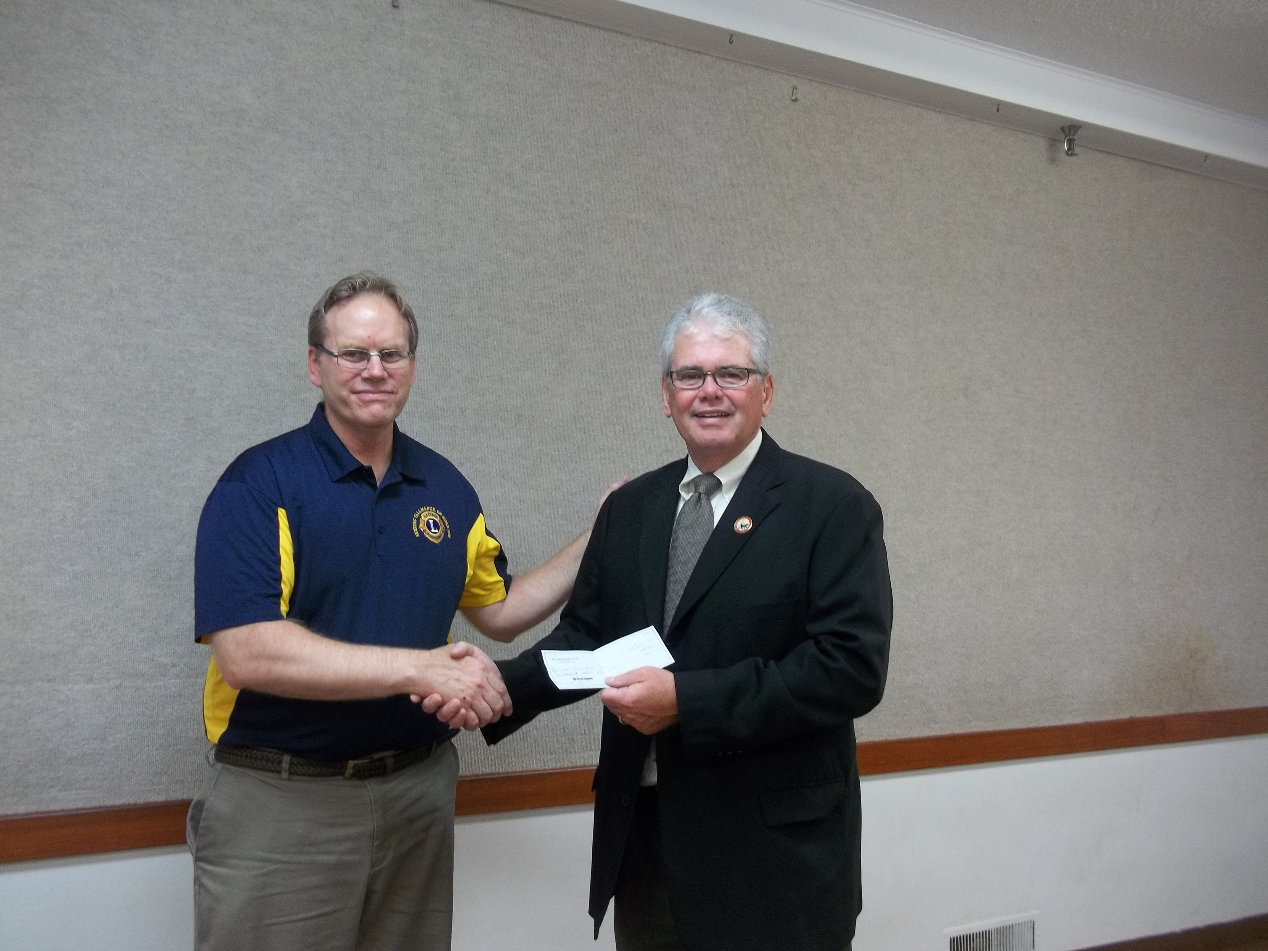 Lion Dan Plazo presents check to PDG Lion Jay Gray, Executive Director of Lions Pilot Dogs of Columbus OH.
